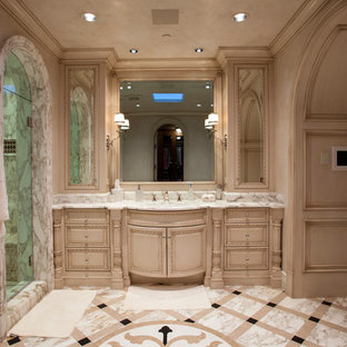 Tuscan beige tile multicolored floor bathroom photo in Orange County with furniture-like cabinets, beige cabinets, beige walls, an undermount sink, a hinged shower door and white countertops