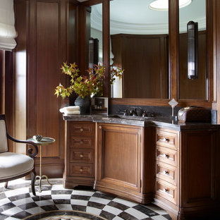 This is an example of a mediterranean ensuite bathroom in Orange County with recessed-panel cabinets, medium wood cabinets, brown walls, a submerged sink and multi-coloured floors.