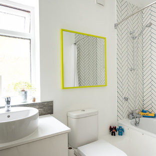 Small bohemian family bathroom in London with white cabinets, a shower/bath combination, white tiles, ceramic tiles, white walls, a built-in bath, a vessel sink, a two-piece toilet and white worktops.