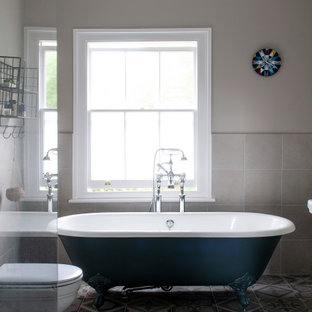 Medium sized traditional ensuite bathroom in London with a freestanding bath, a two-piece toilet, beige walls, mosaic tile flooring and grey floors.