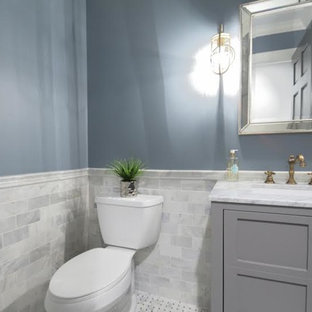 Example of a small transitional gray tile and stone tile marble floor and gray floor bathroom design in Chicago with recessed-panel cabinets, gray cabinets, a two-piece toilet, blue walls, an undermount sink and marble countertops