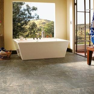Diseño de cuarto de baño principal, clásico renovado, grande, con bañera exenta, paredes amarillas, baldosas y/o azulejos de piedra, baldosas y/o azulejos grises, suelo de pizarra y suelo gris
