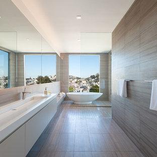 Foto di una stanza da bagno padronale moderna di medie dimensioni con lavabo rettangolare, ante lisce, ante beige, top in superficie solida, vasca freestanding, doccia aperta, piastrelle grigie, piastrelle in pietra, pareti bianche, pavimento in marmo e doccia aperta