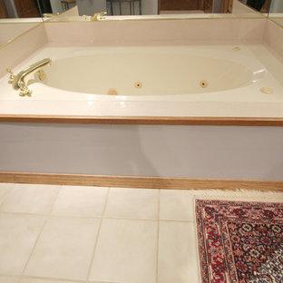 Diseño de cuarto de baño principal, clásico, de tamaño medio, con lavabo integrado, armarios con paneles con relieve, puertas de armario de madera oscura, encimera de mármol, bañera esquinera, baldosas y/o azulejos beige, paredes beige y suelo de baldosas de porcelana
