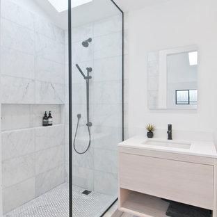 Modelo de cuarto de baño principal, moderno, pequeño, con armarios con paneles lisos, puertas de armario de madera clara, ducha abierta, sanitario de una pieza, baldosas y/o azulejos blancos, baldosas y/o azulejos de mármol, paredes blancas, suelo de cemento, lavabo encastrado, encimera de cuarzo compacto, suelo gris, ducha abierta y encimeras blancas