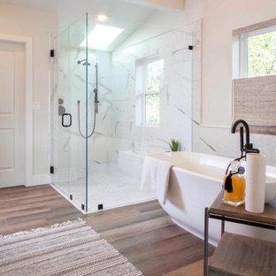На фото: большая главная ванная комната в морском стиле с плоскими фасадами, искусственно-состаренными фасадами, отдельно стоящей ванной, душем без бортиков, унитазом-моноблоком, белой плиткой, керамогранитной плиткой, белыми стенами, полом из ламината, врезной раковиной, столешницей из искусственного кварца, бежевым полом, душем с распашными дверями, белой столешницей, сиденьем для душа, тумбой под две раковины, встроенной тумбой и сводчатым потолком с