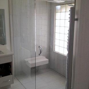 Esempio di un'ampia stanza da bagno con doccia contemporanea con lavabo sottopiano, ante grigie, top in quarzite, doccia a filo pavimento, piastrelle grigie e piastrelle in pietra
