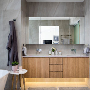 Design ideas for a large contemporary master bathroom in Sunshine Coast with flat-panel cabinets, medium wood cabinets, a freestanding tub, an open shower, gray tile, grey walls, an undermount sink and grey floor.