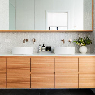 Photo of a midcentury bathroom in Canberra - Queanbeyan with flat-panel cabinets, medium wood cabinets, gray tile, mosaic tile, a vessel sink, black floor and white benchtops.