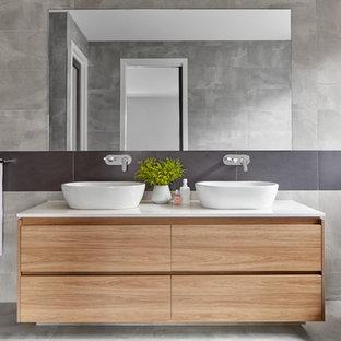 Idéer för att renovera ett funkis vit vitt en-suite badrum, med släta luckor, skåp i ljust trä, ett fristående badkar, grå kakel, grå väggar, ett fristående handfat och grått golv