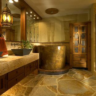 Modelo de cuarto de baño principal, rústico, de tamaño medio, con bañera japonesa, lavabo sobreencimera, encimera de azulejos, armarios estilo shaker, puertas de armario de madera en tonos medios, ducha esquinera, baldosas y/o azulejos en mosaico, paredes beige, suelo de pizarra, baldosas y/o azulejos marrones y encimeras amarillas