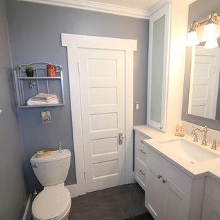Ejemplo de cuarto de baño con ducha, de estilo americano, de tamaño medio, con lavabo integrado, armarios con rebordes decorativos, puertas de armario blancas, encimera de cuarzo compacto, sanitario de una pieza, baldosas y/o azulejos grises, baldosas y/o azulejos de porcelana, paredes grises y suelo de baldosas de porcelana
