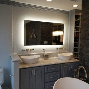 ヒューストンの広いトラディショナルスタイルのおしゃれなマスターバスルーム (シェーカースタイル扉のキャビネット、グレーのキャビネット、置き型浴槽、ダブルシャワー、男性用トイレ、グレーのタイル、大理石タイル、グレーの壁、大理石の床、ベッセル式洗面器、大理石の洗面台、白い床、開き戸のシャワー) の写真