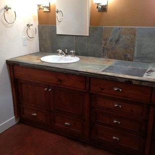 Foto di una stanza da bagno padronale tradizionale di medie dimensioni con lavabo da incasso, ante in legno scuro, pareti multicolore, consolle stile comò, pavimento in cemento, WC a due pezzi, piastrelle grigie, piastrelle in ardesia, top piastrellato e pavimento marrone