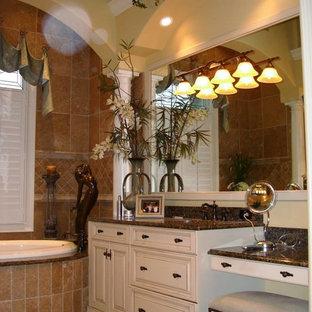 Imagen de cuarto de baño principal, clásico, de tamaño medio, con armarios con paneles con relieve, puertas de armario blancas, bañera encastrada, baldosas y/o azulejos beige, baldosas y/o azulejos de terracota, paredes amarillas, suelo de travertino, lavabo bajoencimera y encimera de granito