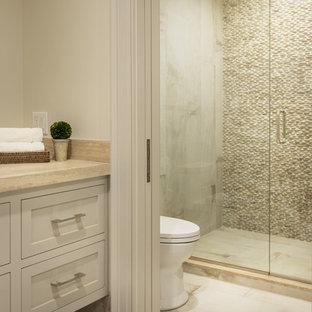 Immagine di una piccola stanza da bagno per bambini minimalista con ante beige, doccia alcova, WC a due pezzi, piastrelle beige, piastrelle di ciottoli, pareti beige, lavabo sottopiano, top in pietra calcarea, pavimento beige e porta doccia scorrevole