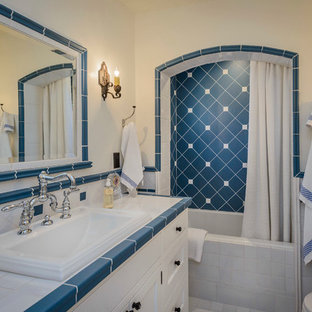 Idee per una stanza da bagno country con lavabo da incasso, ante con riquadro incassato, ante bianche, top piastrellato, piastrelle blu, piastrelle diamantate, vasca ad alcova, vasca/doccia e pareti bianche