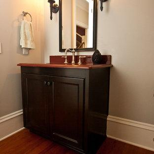 Immagine di una piccola stanza da bagno con doccia con ante con bugna sagomata, ante nere, WC a due pezzi, pareti beige, pavimento in legno massello medio, lavabo sottopiano, top in superficie solida, pavimento arancione e top rosso