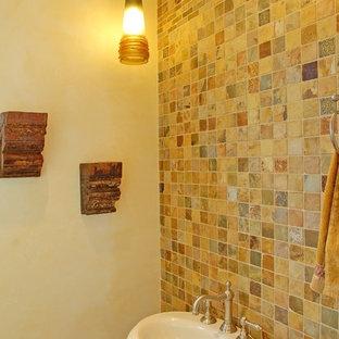 Esempio di una stanza da bagno con doccia mediterranea di medie dimensioni con piastrelle beige, piastrelle in ceramica, pareti beige, lavabo a colonna, ante in stile shaker, ante in legno chiaro, pavimento in pietra calcarea, top in pietra calcarea, pavimento beige e WC monopezzo