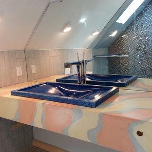 Diseño de cuarto de baño principal, bohemio, de tamaño medio, con ducha empotrada, baldosas y/o azulejos grises, baldosas y/o azulejos en mosaico, paredes grises, suelo de baldosas de porcelana, lavabo encastrado, encimera de cemento, suelo gris y ducha con puerta con bisagras
