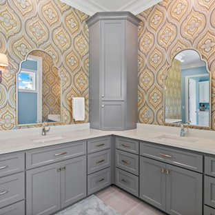 Example of a large beach style master multicolored tile and stone slab porcelain tile, beige floor, single-sink and wallpaper bathroom design in Raleigh with shaker cabinets, gray cabinets, a two-piece toilet, multicolored walls, an integrated sink, solid surface countertops, white countertops and a freestanding vanity