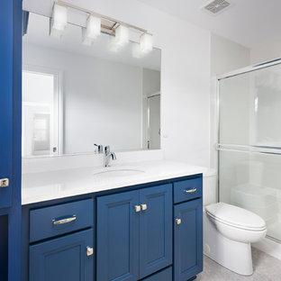 Ejemplo de cuarto de baño infantil, tradicional renovado, con puertas de armario azules, ducha empotrada, sanitario de dos piezas, baldosas y/o azulejos azules, baldosas y/o azulejos de vidrio laminado, paredes blancas, suelo de baldosas de cerámica, lavabo bajoencimera, suelo gris y ducha con puerta corredera