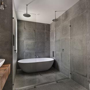 Imagen de cuarto de baño principal, industrial, grande, con bañera exenta, ducha doble, baldosas y/o azulejos grises, paredes grises, suelo de cemento, lavabo sobreencimera, encimera de madera, armarios abiertos, puertas de armario de madera oscura, sanitario de pared y encimeras marrones
