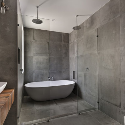 Inspiration for a large industrial master gray tile concrete floor bathroom remodel in San Diego with gray walls, a vessel sink, wood countertops, open cabinets, medium tone wood cabinets, a wall-mount toilet and brown countertops