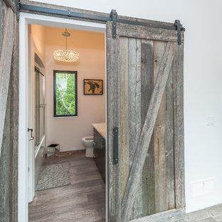 他の地域の中サイズのコンテンポラリースタイルのおしゃれなバスルーム (浴槽なし) (フラットパネル扉のキャビネット、黒いキャビネット、アルコーブ型浴槽、シャワー付き浴槽、グレーの壁、濃色無垢フローリング、アンダーカウンター洗面器、珪岩の洗面台、茶色い床、引戸のシャワー、白い洗面カウンター) の写真
