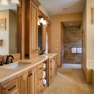 Drop-in bathtub - craftsman brown tile beige floor drop-in bathtub idea in Portland with raised-panel cabinets, medium tone wood cabinets, beige walls, an undermount sink and beige countertops