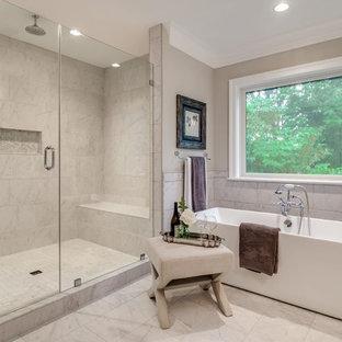 Inredning av ett amerikanskt stort en-suite badrum, med släta luckor, vita skåp, ett fristående badkar, en öppen dusch, en toalettstol med hel cisternkåpa, vit kakel, porslinskakel, grå väggar, klinkergolv i porslin, ett nedsänkt handfat, marmorbänkskiva, vitt golv och dusch med gångjärnsdörr