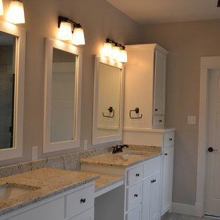 Ejemplo de cuarto de baño principal, de estilo americano, de tamaño medio, con lavabo integrado, armarios con paneles empotrados, puertas de armario blancas, encimera de granito, ducha esquinera, baldosas y/o azulejos blancos y paredes beige