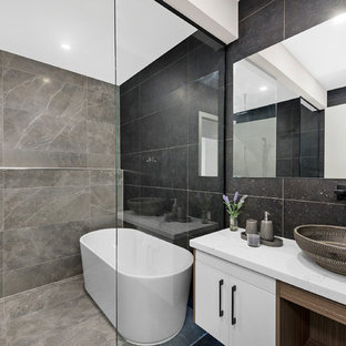 Inspiration for a contemporary master bathroom in Canberra - Queanbeyan with flat-panel cabinets, white cabinets, a freestanding tub, an open shower, gray tile, grey walls, a vessel sink, marble benchtops and grey floor.
