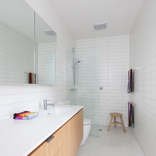 Photo of a midcentury 3/4 bathroom in Melbourne with flat-panel cabinets, light wood cabinets, a curbless shower, white tile, white walls, mosaic tile floors, an undermount sink, white floor, an open shower and white benchtops.