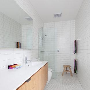 Imagen de cuarto de baño con ducha, vintage, con armarios con paneles lisos, puertas de armario de madera clara, ducha a ras de suelo, baldosas y/o azulejos blancos, paredes blancas, suelo con mosaicos de baldosas, lavabo bajoencimera, suelo blanco, ducha abierta y encimeras blancas