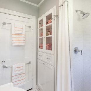 Diseño de cuarto de baño con ducha, clásico, pequeño, con armarios tipo vitrina, puertas de armario blancas, encimera de mármol, sanitario de una pieza, baldosas y/o azulejos blancos, baldosas y/o azulejos de cemento, paredes grises, suelo con mosaicos de baldosas, ducha abierta, suelo blanco y ducha con cortina