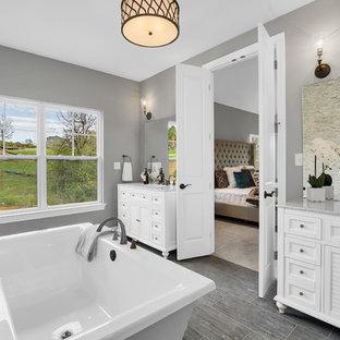 Immagine di una stanza da bagno padronale in campagna con vasca freestanding, piastrelle in ceramica, pareti multicolore, pavimento con piastrelle in ceramica, top in granito, ante a persiana, ante bianche, lavabo sottopiano e pavimento grigio