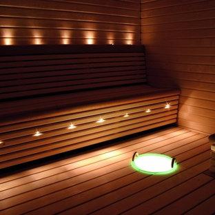 Ejemplo de sauna minimalista, de tamaño medio, con paredes marrones, suelo de madera en tonos medios y suelo marrón