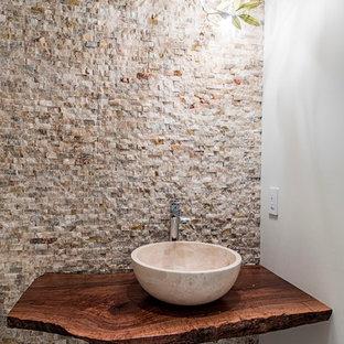 Foto de cuarto de baño con ducha, contemporáneo, pequeño, con sanitario de dos piezas, baldosas y/o azulejos de piedra, lavabo sobreencimera, baldosas y/o azulejos marrones, paredes marrones, suelo de mármol y encimera de madera