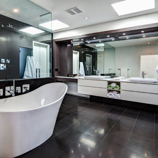 Bathroom - large contemporary master black tile and stone tile ceramic floor and black floor bathroom idea in Calgary with a vessel sink, flat-panel cabinets, white cabinets, quartzite countertops, a bidet and white walls