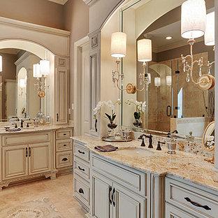 Esempio di una grande stanza da bagno padronale classica con ante con bugna sagomata, ante beige, doccia alcova, piastrelle beige, piastrelle in travertino, pareti beige, pavimento in travertino, lavabo sottopiano, top in granito, pavimento beige e porta doccia a battente
