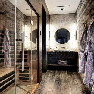 Idée de décoration pour un grand sauna design avec un placard sans porte, des portes de placard en bois sombre, un plan de toilette en bois, un sol en bois foncé et un mur gris.