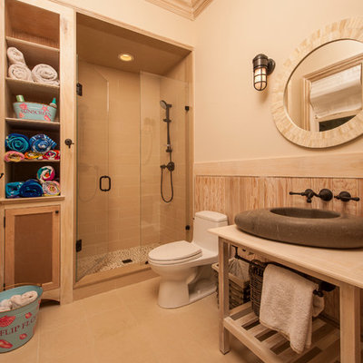Elegant beige tile alcove shower photo in Raleigh with a vessel sink, furniture-like cabinets, light wood cabinets and a one-piece toilet