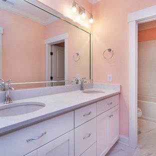 シャーロットの中くらいのおしゃれなマスターバスルーム (落し込みパネル扉のキャビネット、白いキャビネット、アルコーブ型浴槽、シャワー付き浴槽、分離型トイレ、白いタイル、サブウェイタイル、ピンクの壁、磁器タイルの床、アンダーカウンター洗面器、珪岩の洗面台、グレーの床、シャワーカーテン、白い洗面カウンター) の写真