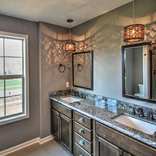 Ejemplo de cuarto de baño principal, clásico, de tamaño medio, con puertas de armario de madera oscura, encimera de granito, baldosas y/o azulejos grises, paredes grises y suelo de baldosas de cerámica