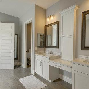Inspiration pour une salle de bain principale craftsman de taille moyenne avec un placard à porte shaker, des portes de placard blanches, un WC à poser, un carrelage blanc, carrelage en mosaïque, un mur gris, un sol en contreplaqué, un lavabo encastré et un plan de toilette en carrelage.