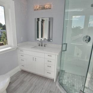 На фото: маленькая ванная комната в современном стиле с плоскими фасадами, белыми фасадами, угловым душем, раздельным унитазом, серой плиткой, белой плиткой, удлиненной плиткой, фиолетовыми стенами, деревянным полом, душевой кабиной, врезной раковиной и столешницей из искусственного камня