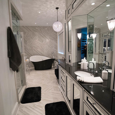 Example of a large minimalist master gray tile, white tile and porcelain tile porcelain tile and gray floor bathroom design in Cleveland with white cabinets, white walls, an undermount sink, solid surface countertops, a hinged shower door and black countertops