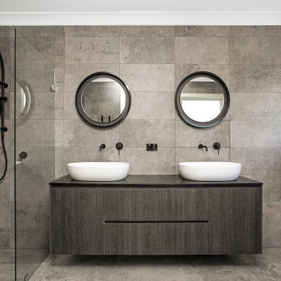 Photo of a contemporary bathroom in Sydney with flat-panel cabinets, grey cabinets, gray tile, a vessel sink, grey floor, black benchtops and a double vanity.