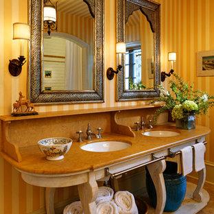 Diseño de cuarto de baño principal, mediterráneo, grande, con ducha doble, sanitario de una pieza, baldosas y/o azulejos de cerámica, paredes amarillas, suelo de mármol, lavabo tipo consola, armarios tipo mueble, puertas de armario de madera clara, encimera de cuarzo compacto y encimeras naranjas